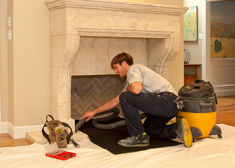 A thorough chimney sweep is performed. The area is draped for protection of floor and furnishing.